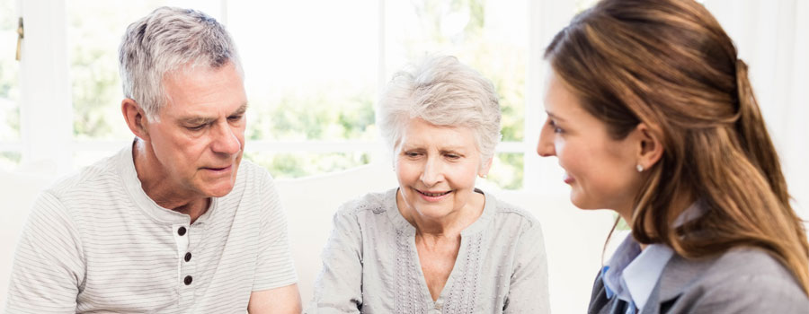 elderly couple having a conversation with clinician