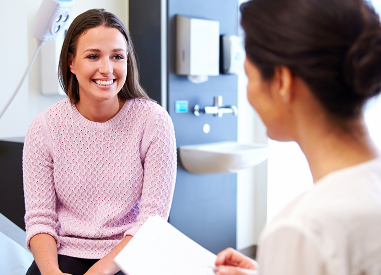 Woman speaking with female nurse in medical setting
