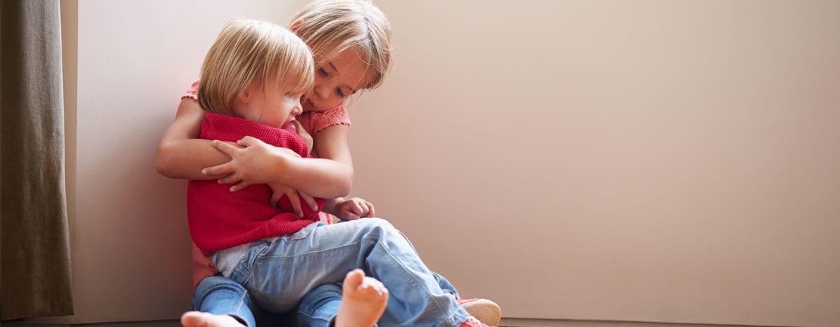 sister embracing scared sibling