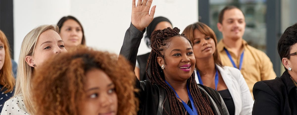 woman raising hand to ask question