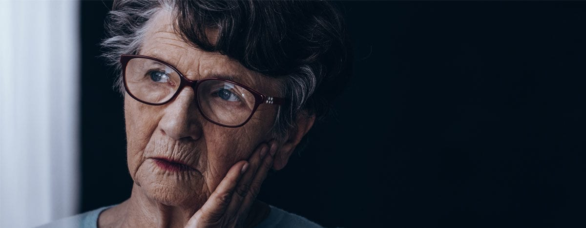 worried elderly woman looking out window