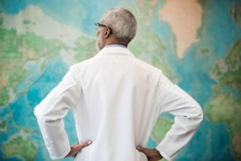 doctor posing in front of world map