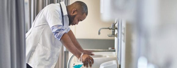 stressed doctor sighing over sink in hospital