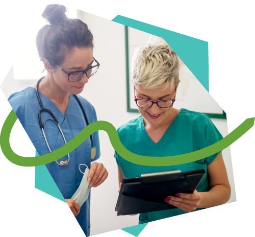 Two healthcare workers look at information on a tablet.