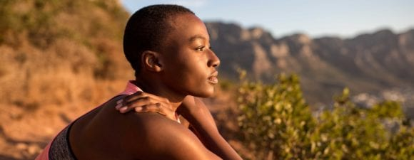Black woman looking out on desert hiking trail.